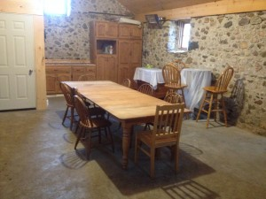 Inside The Olde Piggery... table and chairs, toilet, counter space with outlet for crock pot, wood fireplace.